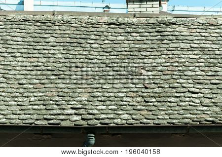 Vintage roof tiles on old house. Aged and grunge roof tiles.