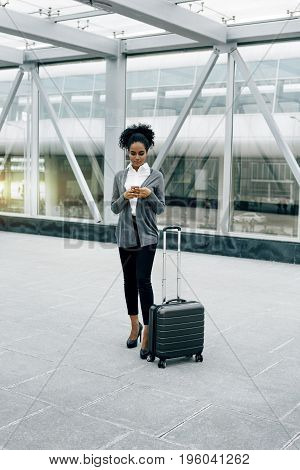 Front view of young businesswoman standing with baggage at airport