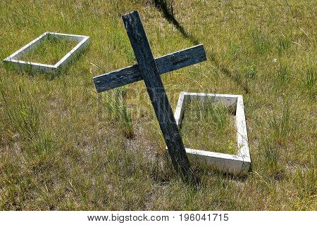 Leaning cross and two old wooden boxes indicate the graveside of children buried in a remote prairie cemetery