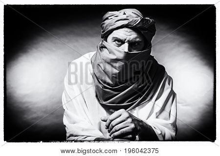 Vintage Black And White Photo Of Berber Man Wearing Turban With Robe. Leaning On Cane. Studio Shot.