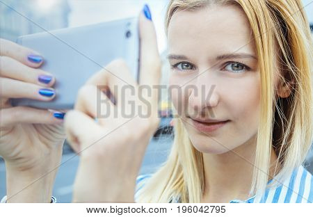 Blonde-haired girl in a striped shirt, uses mobile flashlight, on a cloudy day, outdoor. . She takes pictures on the smartphone, holding it with both hands, on the background of houses.Purple manicure