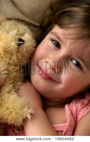A young girl playing with her teddy bear