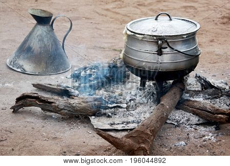 Cooking corn cereal in contrule on fire in the village Botswana