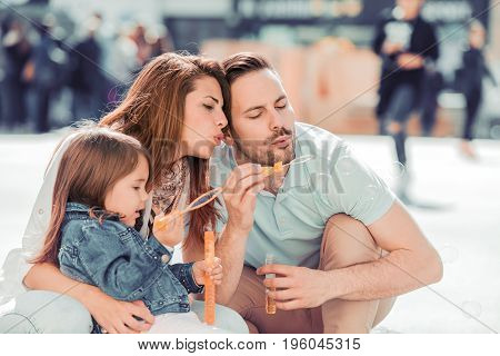 Happy family with one child having fun together in summer city.