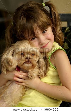 A young girl loving on her puppy