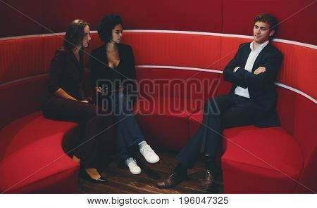 Two businesswomen (caucasian and black with curly afro hair) looking angry on their male colleague in business suit because he came to their sofa in office chillout during their private conversation