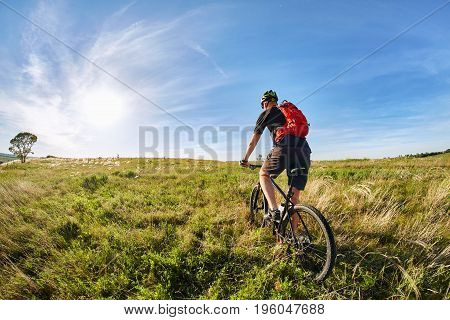 Traveler with backpack Riding the Bike on the Beautiful Spring Mountain Trail against Blue sky