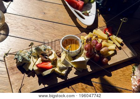 snack lying on the table buffet with cheese, honey and grapes on a wooden tray