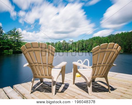 Long exposure of lake and clouds viewed from two empty muskoka chairs on a sunny summer day