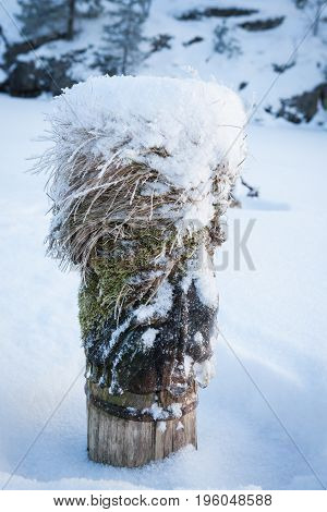 Snow covered wooden pole at frozen lake