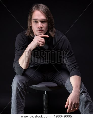 Portrait of thinking brunette young man on black background