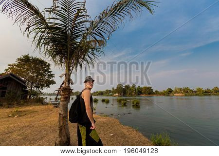 Young male tourist walking across Don Det island in south Laos. Landscape of nature on four thousands islands Si Phan Don on Mekhong river in south east asia during summer.