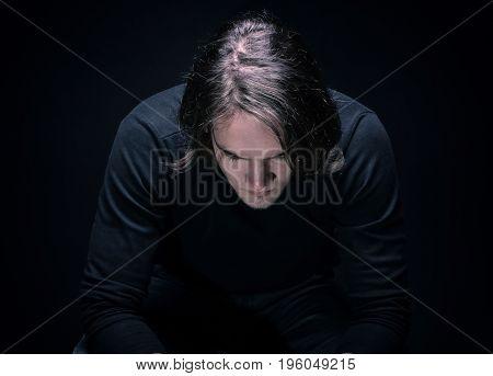 Depressive brunette young man on black background