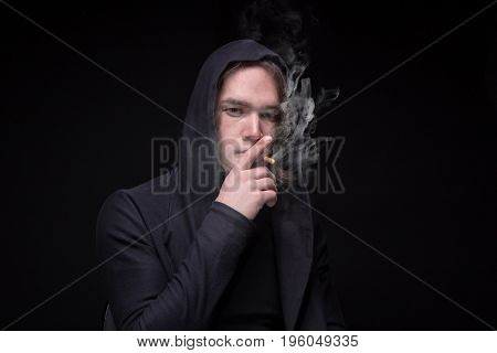 Smoking brunette man in the hood on black background