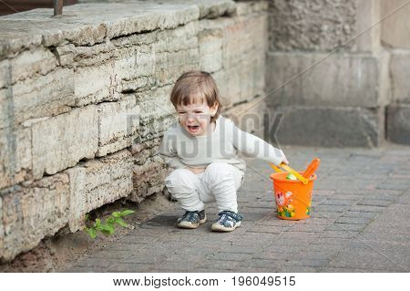 Little Boy With Long Blond Hair Crying Standing On The Street. In His Hand He Is Holding An Orange B