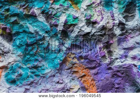 Stone wall stained colorful patches of bright colors aerosols, Modern iconic urban culture of street youth, stylish pattern, fashion colors, abstract background.