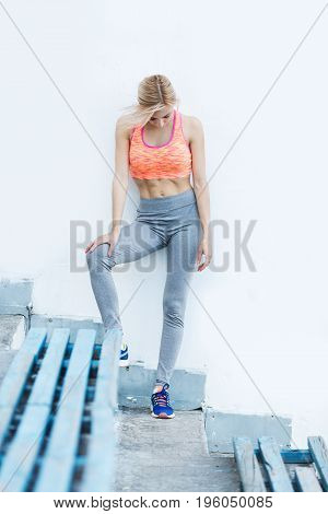 Female athlete taking break after running training. Woman resting after jogging. Fitness and workout wellness concept