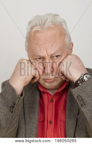 Elderly person pouts with his face in his hands - on bright background