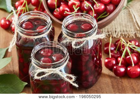 Cherry jam on wooden ground with fresh cherries