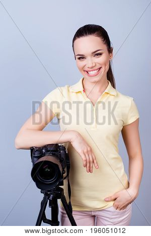 Cute Female Photographer With Beaming Smile Is Standing Near The Camera In Casual Clothes On The Pur