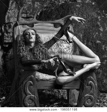 Girl In Big Wooden Arm Chair With Fur In Forest
