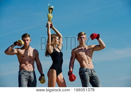 Woman And Twins With Muscular Body Hold Champion Cup.