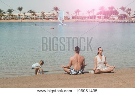 family vacation. family of happy child man and woman meditating in yoga pose in sea ocean water on sand at sunny summer beach in morning idyllic vacation relax healthy lifestyle