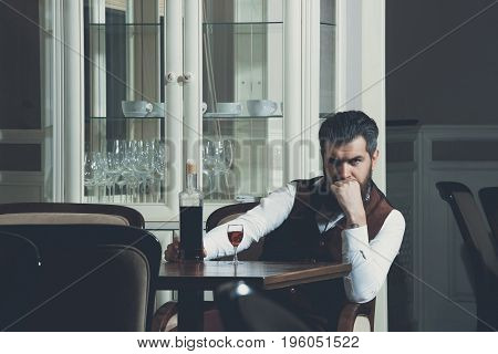 Man Sitting At Table Served With Bottle And Glass