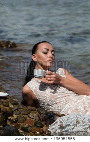 fashion and beauty. pretty girl or sexy woman with long brunette hair ponytail in white dress drinking coffee in clear sea or ocean water on sunny seascape background. Idyllic summer vacation