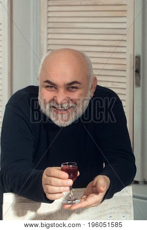Pensioner smiling with glass of wine. Happy man or senior person with grey beard in black sweater in room on wooden window shutters. Alcohol and appetizer. Unhealthy lifestyle and bad habits