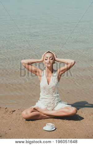 woman meditating sitting in yoga pose in sea ocean water on sand at sunny summer beach with coffee cup in morning idyllic vacation relax healthy lifestyle