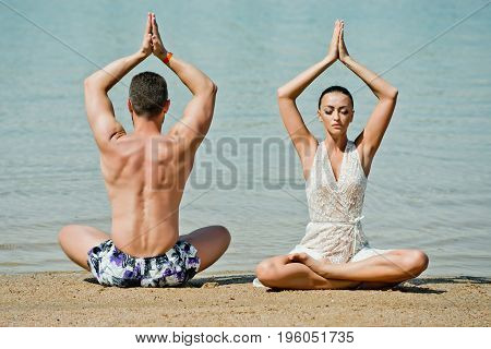 yoga couple. man and woman meditating in yoga pose in sea ocean water on sand at sunny summer beach in morning idyllic vacation relax healthy lifestyle couple in love family
