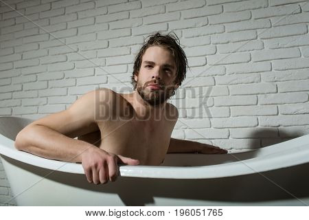 guy sitting in bath tub. man with muscular body in bath. spa and relaxation. hygiene and healthcare. bathroom and home comfort.