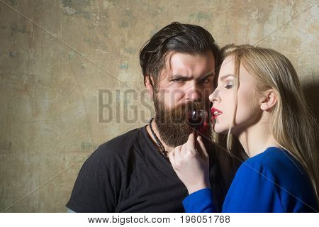 Hipster And Girl Relaxing With Glass Of Red Liqueur