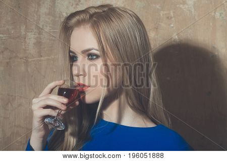 Girl drinking glass of red liqueur. Woman with blond long hair make up in blue dress on beige wall. Alcohol appetizer bad habits addictive and convive. Unhealthy lifestyle