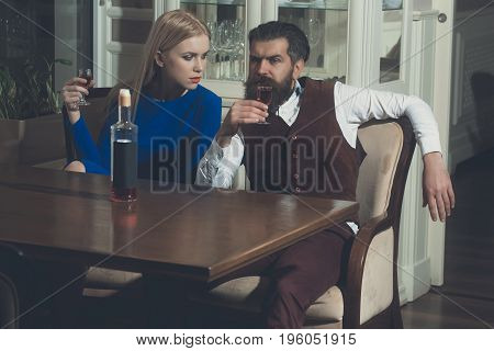 Man And Girl Sharing Bottle Of Red Wine In Restaurant