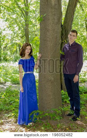 A young guy and a girl are standing on either side of the tree trunk.