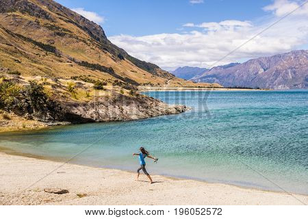 New Zealand travel happy tourist woman running of joy and freedom at beach shore of lake Hawea nature landscape. Near Wanaka, Otago Region