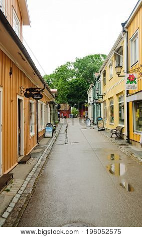 Sigtuna, Sweden-July 10, 2017:Sigtuna, Sweden, shopkeepers on the old main street (Stora Gatan) preparing to open their shops early in the morning