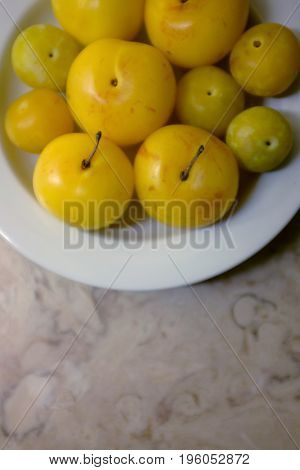Closeup on white plate with juicy yellow plums