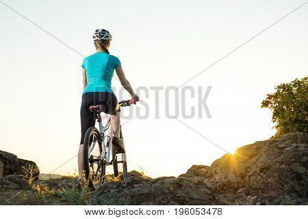 Young Woman Resting with Mountain Bike on the Summer Rocky Trail and Looking at Beautiful Sunset. Travel, Sports and Adventure Concept.