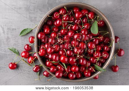 Ripe cherries in the metal plate on a stone slab. Top view.