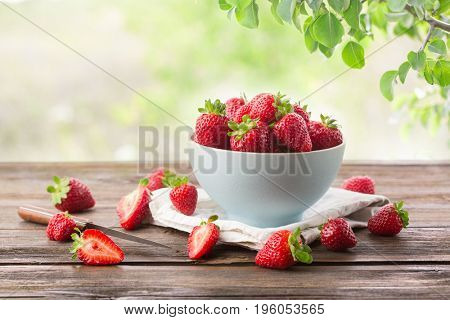 Ripe strawberry from a garden in a bowl on a wooden board on a background of green leaves