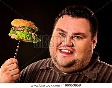 Diet failure of fat man eating fast food hamberger. Happy smile overweight person who spoiled healthy food by eating huge hamburger on fork. Junk meal leads to obesity. He wants a pleasant appetite.