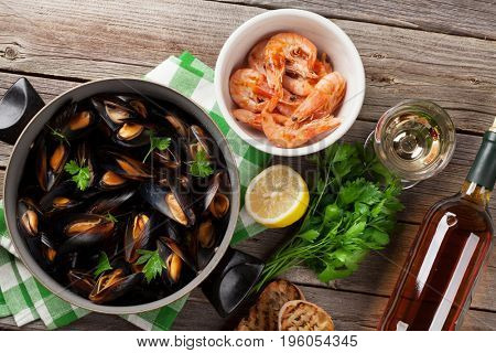 Mussels, prawns and white wine on wooden table. Top view
