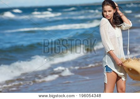 Full length portrait of a young woman in shorts walking on the beach