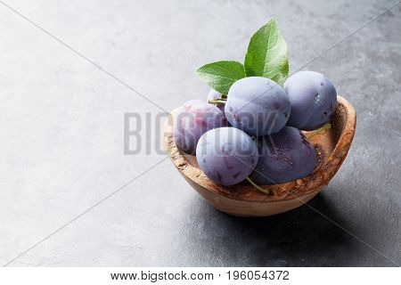 Garden plums in bowl on stone table. View with copy space for your text
