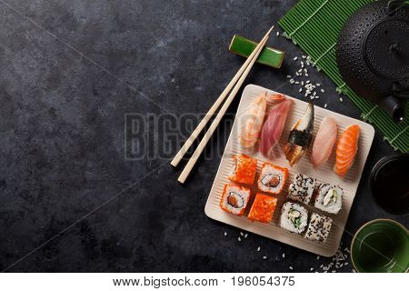 Set of sushi and maki roll and green tea on stone table. View with copy space