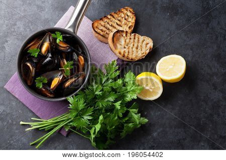 Mussels and bread toasts on stone table. Top view
