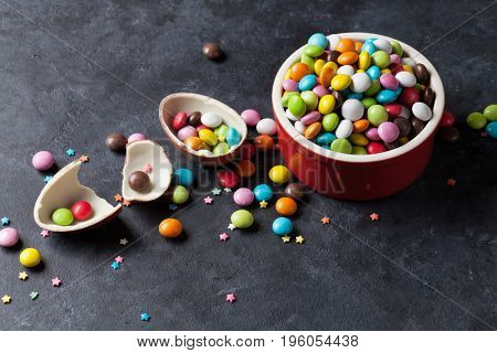 Colorful candies and chocolate egg on stone background